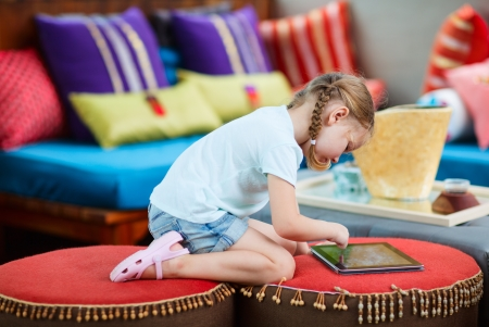 Adorable little girl playing on a tablet device Stock Photo - 17603599
