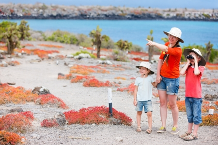 ecotourism: Mother and two kids hiking at scenic terrain Stock Photo