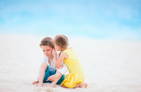 Adorable little girl sharing a secret with her brother photo