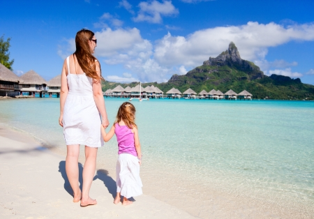otemanu: Mother and daughter at tropical beach enjoying view of Otemanu mountain Stock Photo