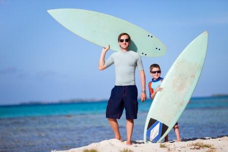 Happy father and son with surfboards at beach photo