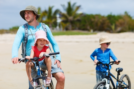 ecotourism: Portrait of father and two kids riding bikes at beach