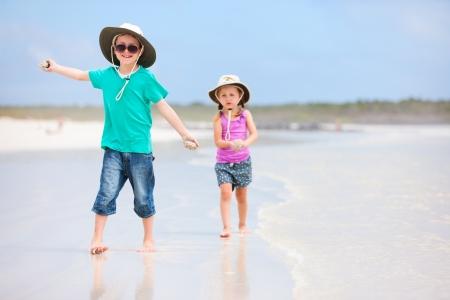 hermanos jugando: Los niños pequeños se ejecutan en la playa tropical Foto de archivo