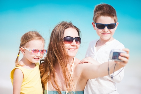 Young mother and her two kids taking self portrait with compact camera photo
