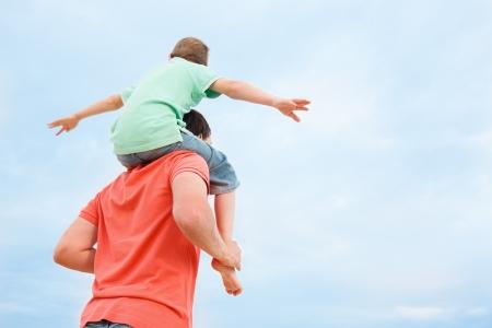 padres: Vista posterior del padre lleva a su hijo sobre los hombros