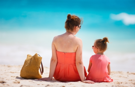 Back view of mother and daughter on a tropical beach photo