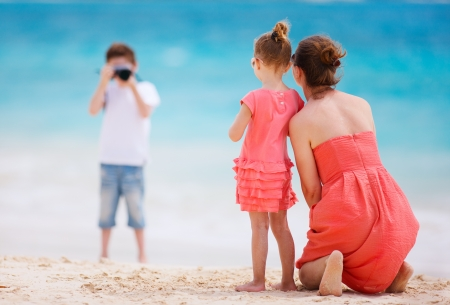 Boy photographing his mother and little sister at tropical beach photo