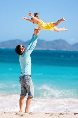Happy father and his adorable little daughter at tropical beach having fun photo