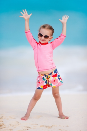 Portrait of cute little girl at tropical beach photo