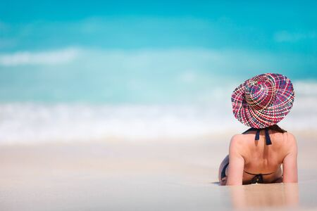 Back view of a young beautiful woman relaxing at tropical beach photo