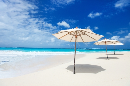 White umbrellas on a beautiful tropical beach at Anguilla, Caribbean photo