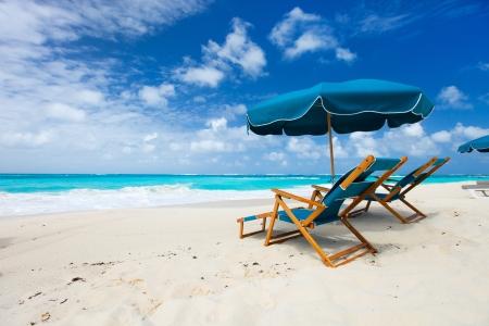 strandstoel: Stoelen en paraplu op een prachtig tropisch strand in Anguilla