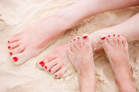 Close up of mother and daughter feet on a tropical sandy beach photo