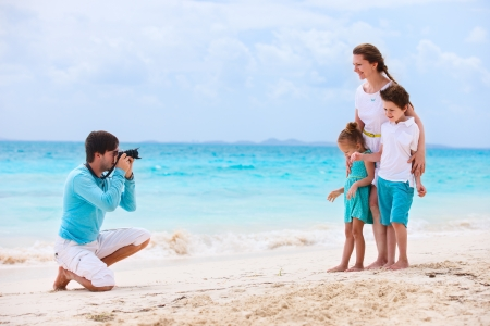 Young man making photo of his wife and kids at tropical beach photo