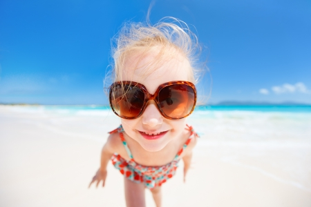 Funny portrait of adorable little girl at tropical beach photo