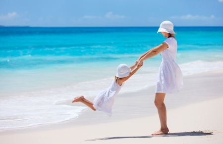 family beach: Mother and daughter having fun at tropical beach