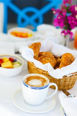 Selection of freshly baked pastry, fruit salad and cappuccino served for breakfast photo
