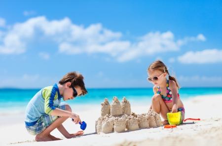 兄と妹の熱帯のビーチで砂の城を作る