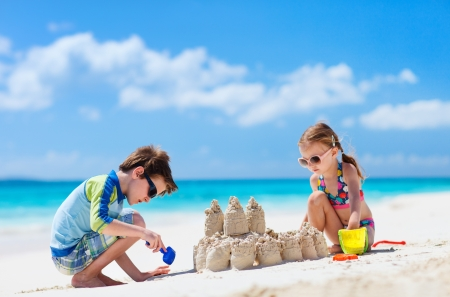 Brother and sister making sand castle at tropical beach Stock Photo