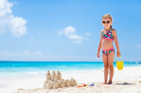Little girl at tropical beach making sand castle photo