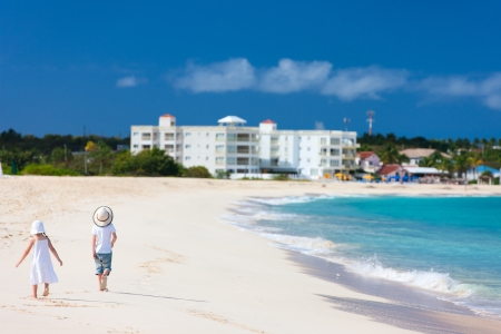 Brother and sister walking along a beach at Caribbean photo