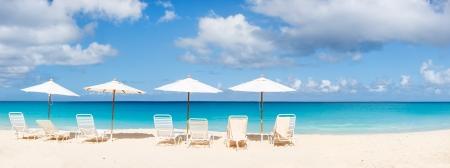 tropical beach panoramic: Chairs and umbrellas on a beautiful Caribbean beach Stock Photo