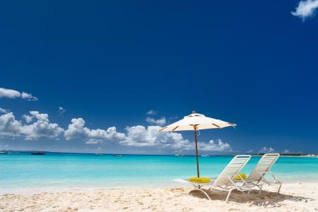 Liegen und Sonnenschirme an einem schönen Strand der Karibik Standard-Bild