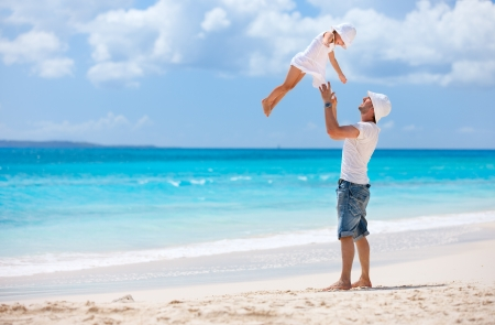 Father and his adorable little daughter at tropical beach having fun photo
