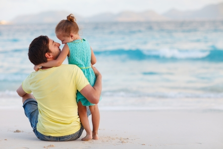 Happy father and his sweet little daughter at beach photo