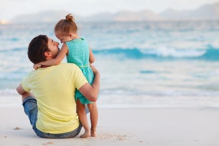 padres: Padre feliz y su pequeña hija dulce en la playa Foto de archivo