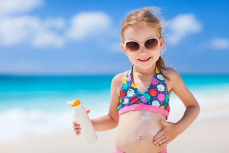 Adorable little girl at tropical beach applying sunblock cream photo