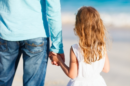 Ni�a adorable que sostiene la mano del padre photo