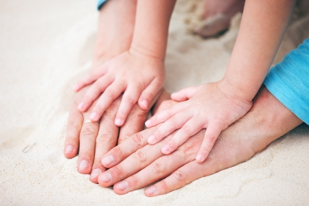 Close up of father and daughter hands on sand  Stock Photo - 18657910