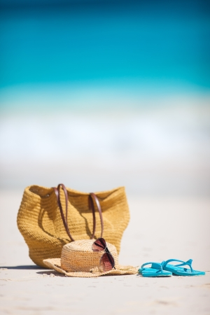 closeup on bags: Straw hat, bag, sun glasses and flip flops on a tropical beach