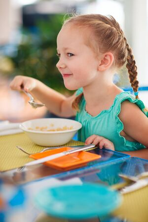mealtime: Adorable little girl having breakfast at resort restaurant