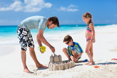 Father and kids making sand castle at tropical beach Stock Photo