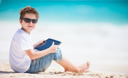 Little boy at beach playing on a tablet device photo
