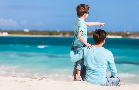 Back view of father and son on beach vacation photo