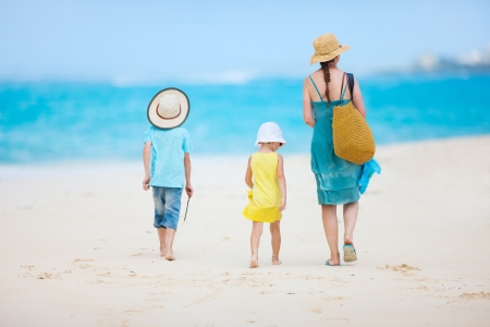 unrecognisable person: Back view of a mother walking with her two kids at tropical beach