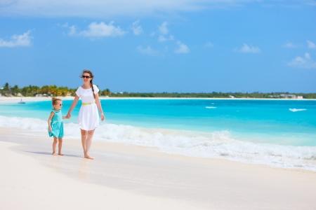 klein meisje op strand: Moeder en dochter wandelen langs een tropisch strand