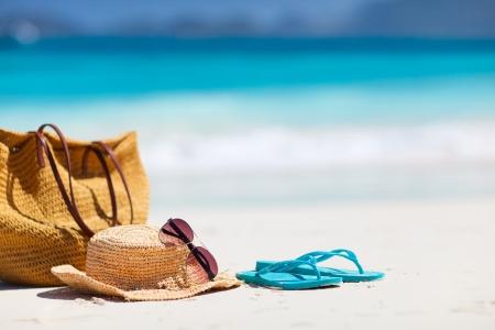 summer: Chapéu de palha, saco, óculos de sol e flip-flops em uma praia tropical Imagens