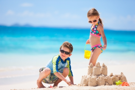 Brother and sister making sand castle at tropical beach photo