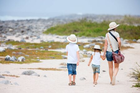ecotourism: Back view of a mother and two kids hiking on Galapagos island of North Seymour
