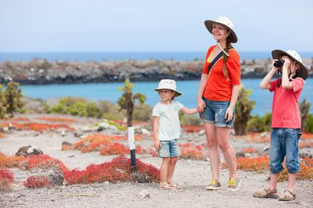 ecotourism: Mother and two kids hiking on Galapagos island of South Plaza Stock Photo