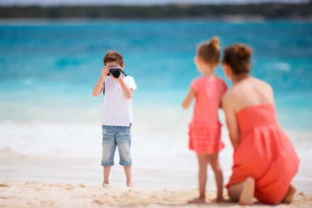 photographing: Boy photographing his mother and little sister at tropical beach
