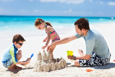 Father and kids making sand castle at tropical beach photo