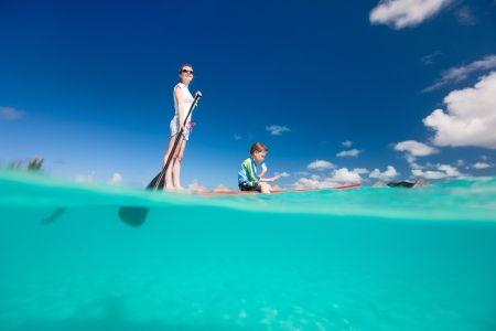 mother board: Mother and son paddling on stand up paddle board