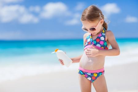 Entzückendes kleines Mädchen am tropischen Strand anwenden Sonnencreme Sahne Standard-Bild