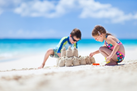 kids playing beach: Brother and sister making sand castle at tropical beach Stock Photo