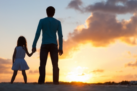father and child: Father and little daughter silhouettes on beach at sunset Stock Photo